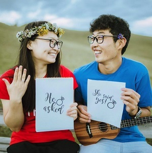 "Couple with signs that read ""He asked"" and ""She said yes!"""