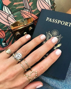 Woman showing wedding band, engagement ring and passport