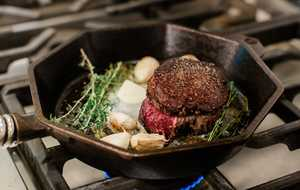 filet mignon in cast iron skillet with herbs