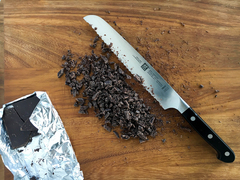 """Bird's eye view of a chopped chocolate bar next to Zwilling Pro 8"""" Bread Knife"""