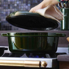 The lid being lifted over Staub's basil 5.75 quart Coq au Vin