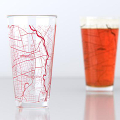 one empty pint glass and one full pint glass each with the map of athens, georiga etched on them