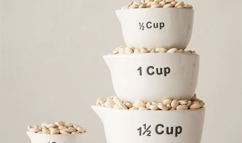 Creative Co-Op Stoneware Measuring Cups, White, Set of 4 with dry beans