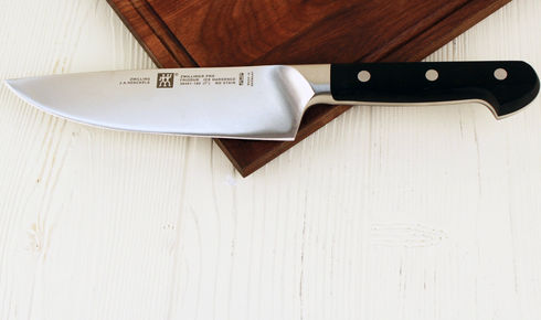 """One Zwilling Pro 7"""" Chef's Knife on cutting board."""