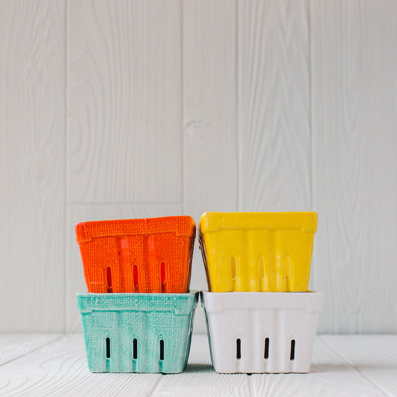 Four Berry Baskets In White, Yellow, Green, And Red Stacked Up From Creative