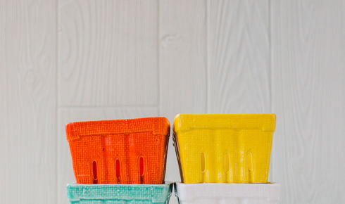 four berry baskets in white, yellow, green, and red stacked up from creative co-op