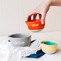 person holding the orange cup of the four measuring cups from creative co-op