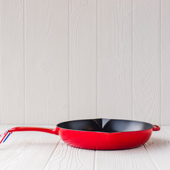 10-inch fry pan in cherry from Staub laying flat