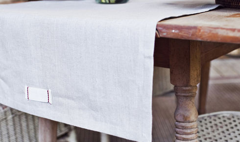 gray linen table runner on wooden rustic table from heirloomed