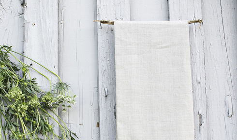 gray linen tea towel from heirloomed outside on gray wooden background