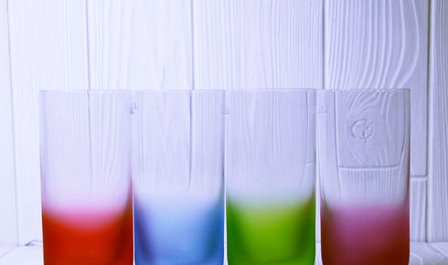 Four LSA Highball glasses in various colors.