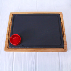 black slate steak plate with red bowl for sauce on wood platter from revol