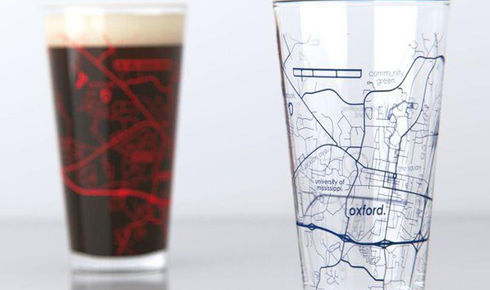 one full and one empty pint glass with map of Oxford, Mississippi etched on them